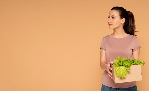 野菜と再利用可能な漫画の箱を運ぶカジュアルな服の女性 無料写真
