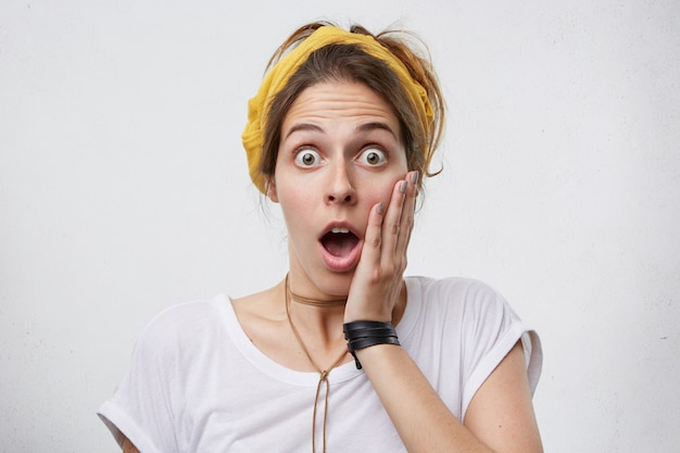 Женщина в повседневной одежде, взявшись за щеку, смотрит с приглушенными глазами и открыла рот в шоке Бесплатные Фотографии