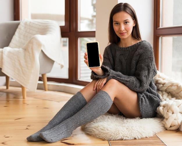 Женщина в уютной одежде сидит на ковре с пустым телефоном Бесплатные Фотографии
