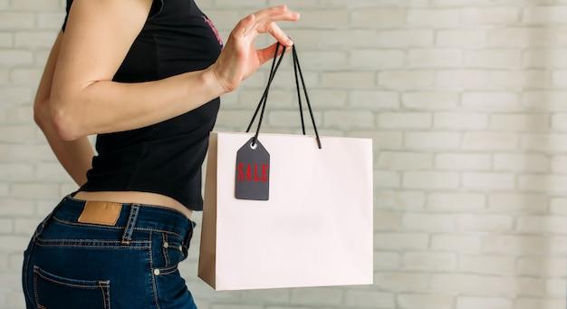 Женщина в джинсовой ткани держит в руке бумажный пакет с биркой у белой кирпичной стены в торговом центре Premium Фотографии