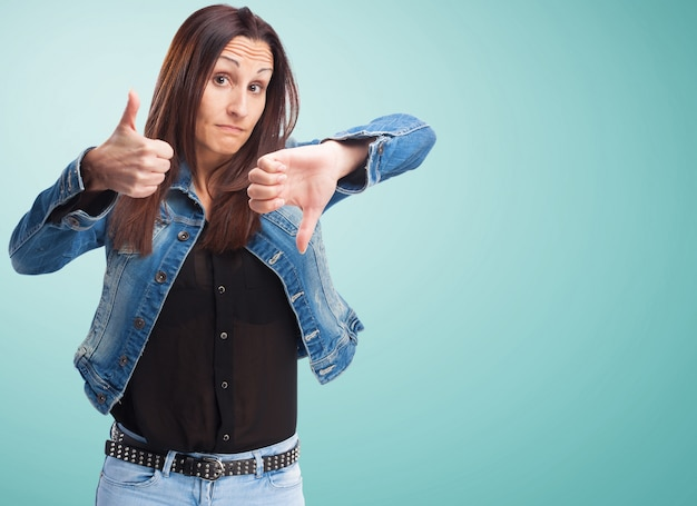 Woman in denim jacket with one thumb up and one down Free Photo
