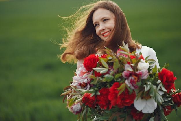 Женщина в элегантном платье, стоя в летнем поле Бесплатные Фотографии