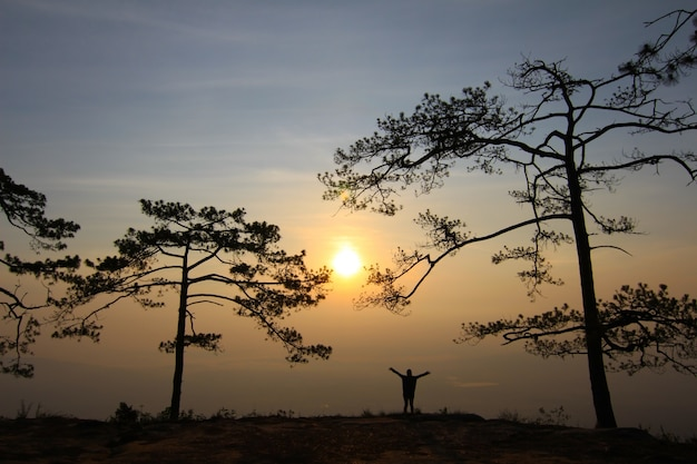 Женщина в вечернем свете с горы и туман на фоне. Premium Фотографии