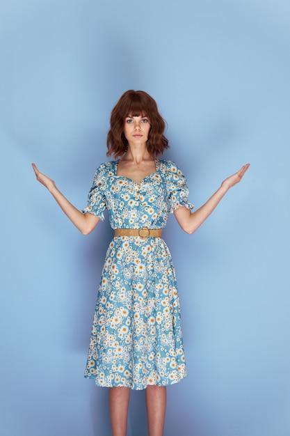 花のドレスを着た女性はあなたの前であなたの手を保持しています Premium写真