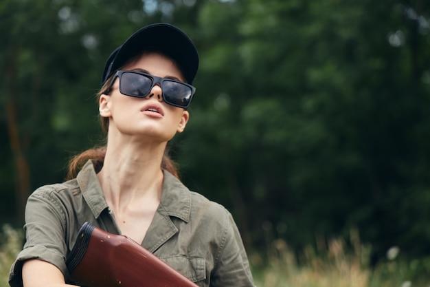 Женщина в лесу с оружием Premium Фотографии