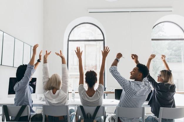大きな光の会議場で同僚の間に座って、手を振っているブロンドの髪のフォーマルなシャツの女性。オフィスでの会議中にストレッチしている疲れたマネージャーの後ろからの写真。 無料写真