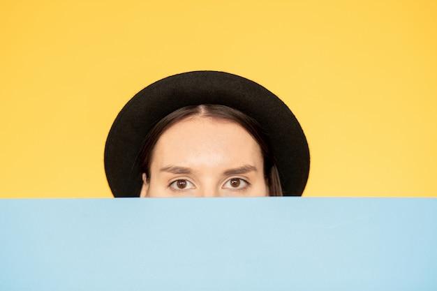 Женщина в шляпе смотрит через стену Premium Фотографии