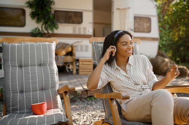 트레일러에서 캠핑 Rv 근처에 앉아 헤드폰에서 여자. 커플은 밴 여행, 캠핑카에서의 낭만적 인 휴가, 캠핑카에서의 캠핑 레저, 캠프 프리미엄 사진