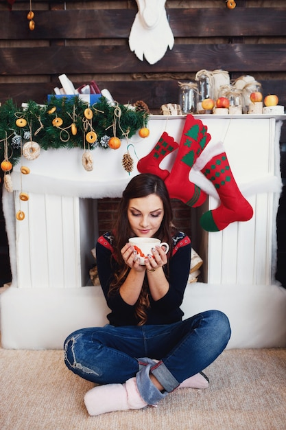 クリスマスのもので飾られた暖炉の前に、ジーンズの女性がホットドリンクのカップと座っている 無料写真