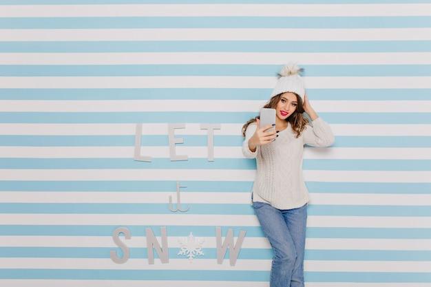 冬の碑文の横で自分撮りをしているジーンズの女性:雪を降らせて 無料写真