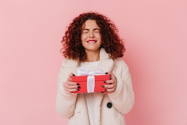 즐거운 기대에 여자는 선물을 보유하고있다. 분홍색 공간에 검은 곱슬 머리를 가진 아가씨. 무료 사진