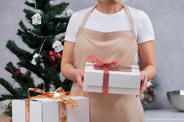 キッチンローブの女性は、クリスマスのお菓子のギフトボックスを保持しています。新年の甘い贈り物。 Premium写真