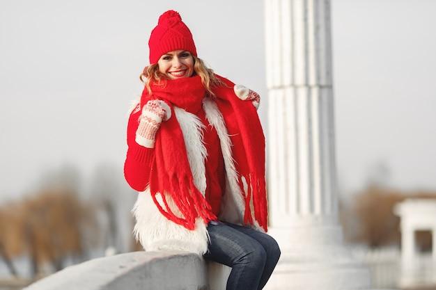 笑顔でカメラを見ているニットの冬の帽子とスカーフの女性 無料写真