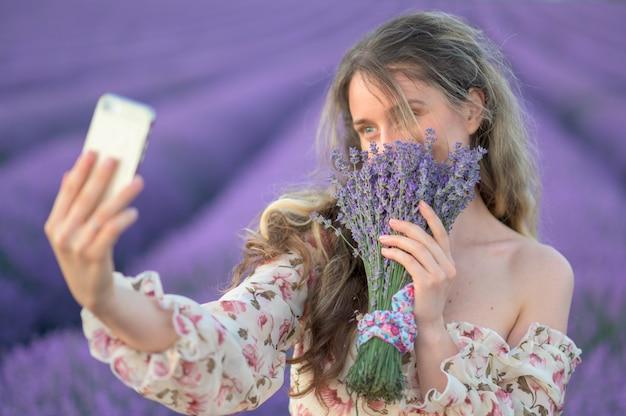 Selfieを取って日没でラベンダー畑の女性 Premium写真