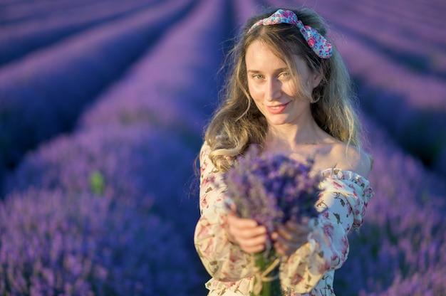 日没で夏のドレスを着てラベンダー畑の女性 Premium写真