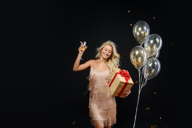 黒の紙吹雪で誕生日やクリスマスパーティーを祝う高級ドレスの女性 Premium写真