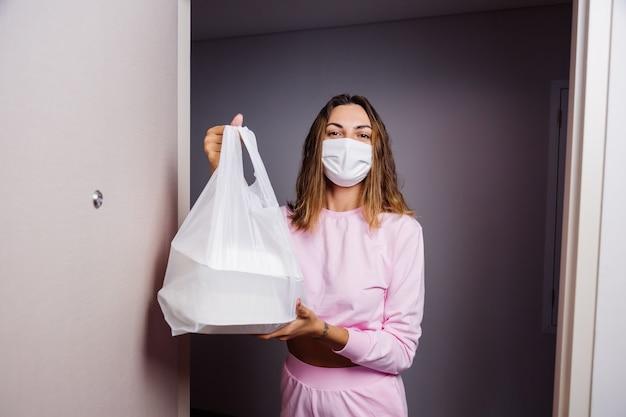 医療用白いフェイスマスクの女性は配達人から食べ物のビニール袋を取得します 無料写真