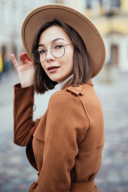 モダンなメガネとファッション帽子と茶色のコートの女性は都市の中心部でポーズをとってください。 無料写真