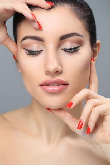 Женщина в обнаженном макияже красный лак для ногтей Бесплатные Фотографии