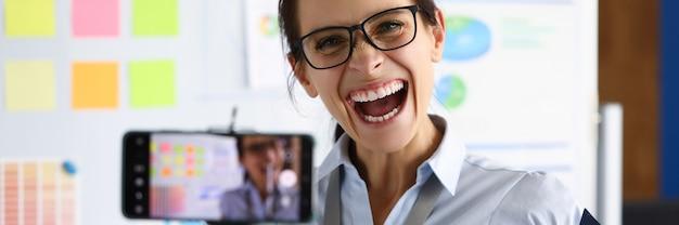 Женщина в офисе радостно кричит, снимая онлайн-трансляцию. эмоциональные всплески настроения концепции Premium Фотографии
