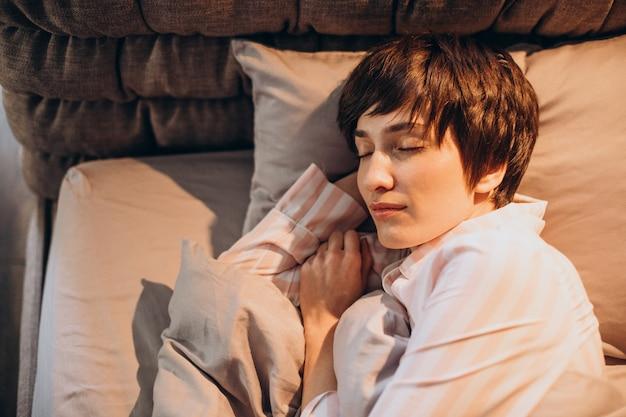 Женщина в пижаме просыпается в постели Бесплатные Фотографии