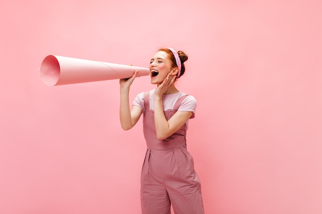 그녀의 귀에 붙어있는 분홍색 옷을 입은 여성이 거대한 종이 조각을 튜브에 감았습니다. 무료 사진