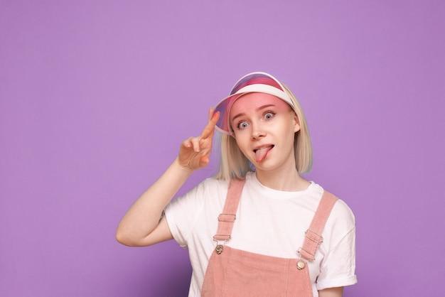 예쁜 캐주얼 드레스에 여자, 분홍색 모자를 쓰고 재미있는 얼굴 만들기 프리미엄 사진