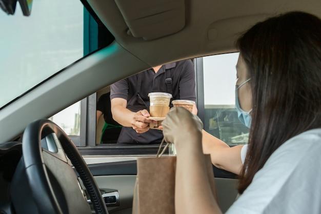 Женщина в защитной маске с кофе во время вспышки коронавируса Premium Фотографии