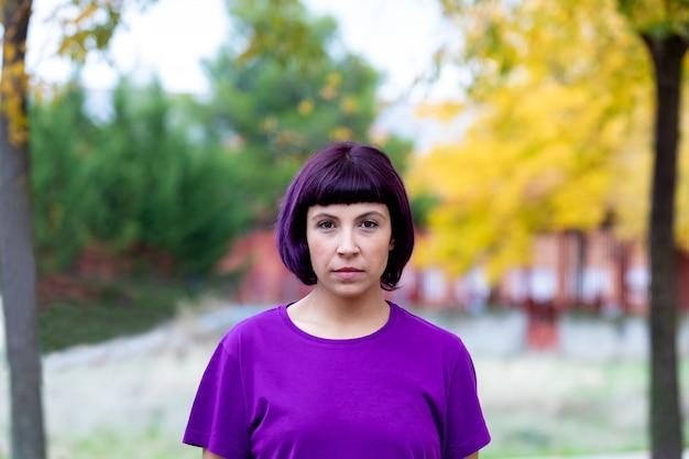 Женщина в пурпуре с желтым деревом предпосылки. Premium Фотографии