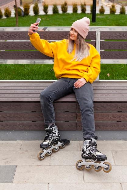 Женщина в роликовых коньках, принимая селфи на скамейке Бесплатные Фотографии