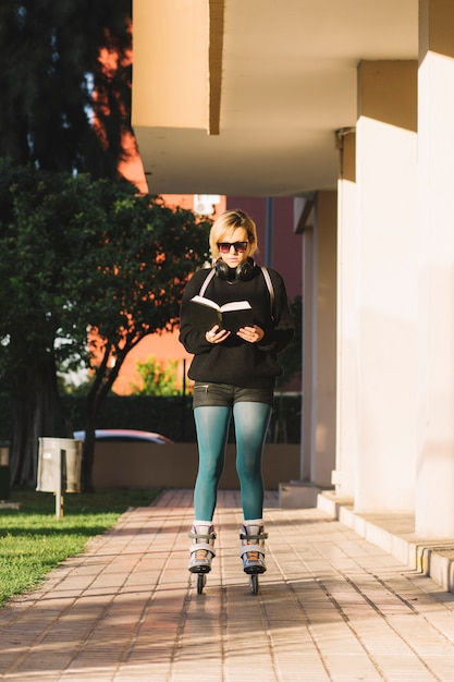 Woman in roller skaters reading book Free Photo
