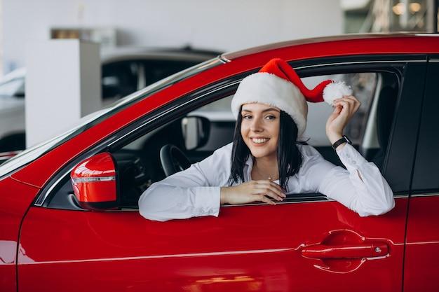 자동차 쇼 룸에서 빨간 자동차로 산타 모자에있는 여자 무료 사진