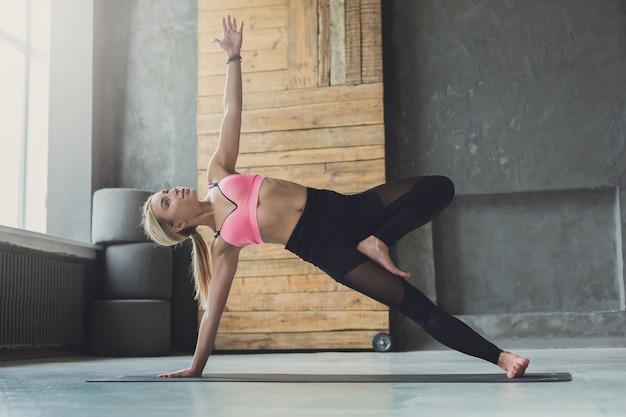 Женщина в позе боковой планки на занятии йогой, упражнение васиштхасана. подходящая девушка-йог, балансирующая на коврике в помещении Premium Фотографии