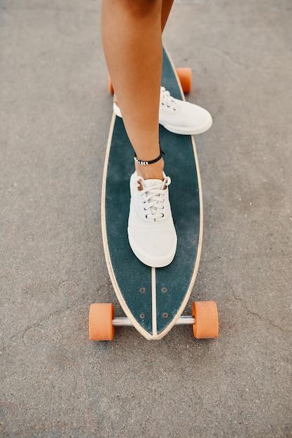 Женщина в кроссовках езда скейтборд открытый на асфальтовой поверхности. Бесплатные Фотографии