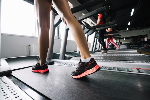 Woman in sneakers walking on treadmill Free Photo