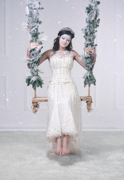 Женщина в костюме снежной королевы на качелях Бесплатные Фотографии