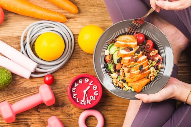 健康的なライフスタイル、健康的な食品を食べる女性と新鮮なサラダの皿を保持しているスポーツウェアの女性 Premium写真