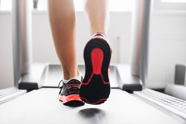 Woman in sports shoes running on treadmill Free Photo