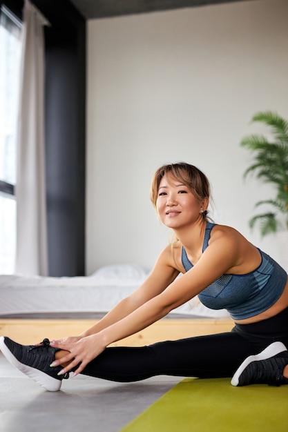 Женщина в спортивной одежде делает фитнес, протягивая ноги, упражнения дома в светлой комнате. концепция спорта, здорового образа жизни и отдыха. Premium Фотографии