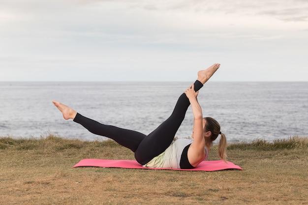 海とピンクのマットに屋外でピラティスをやっているスポーツウェアの女性 Premium写真