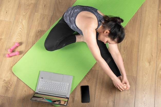 운동복에있는 여자는 원격 요가 운동 요가 클래스를 확인합니다. 여자는 Videocall을 통해 노트북을 사용하여 운동을 스트레칭, 피트니스 운동을합니다. 프리미엄 사진
