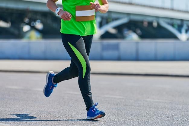 通りを走っているスポーツウェアの女性 Premium写真