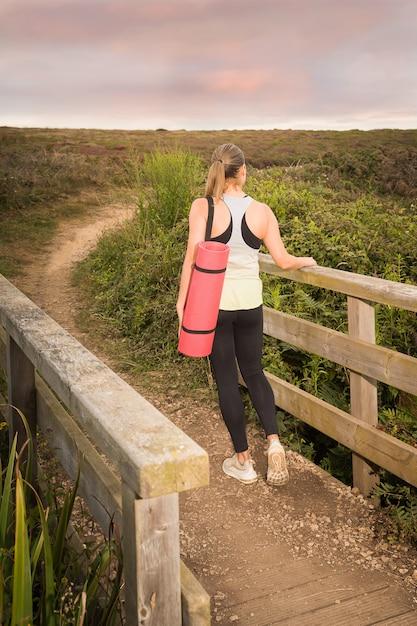 Женщина в спортивной одежде с розовым ковриком гуляет после тренировки в парке на закате Premium Фотографии
