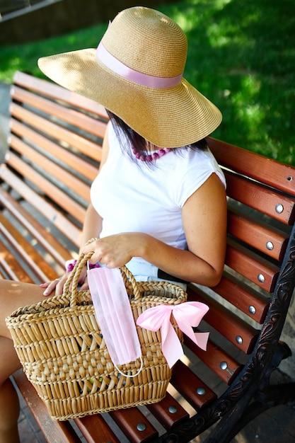 麦わら帽子とピンクの保護マスク付きバッグの女性、街の屋外公園のベンチに座って、コンセプトセルフケア、コロナウイルスパンデミック中の生活、covid-19 Premium写真