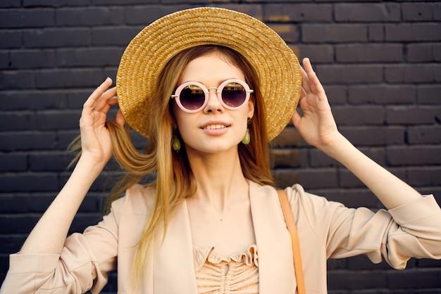 Женщина в солнечных очках и шляпе украшения прогулки на открытом воздухе кирпичной стены на заднем плане. Premium Фотографии