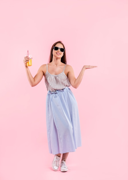 サングラス立っているとジュースのガラスを保持している女性 無料写真