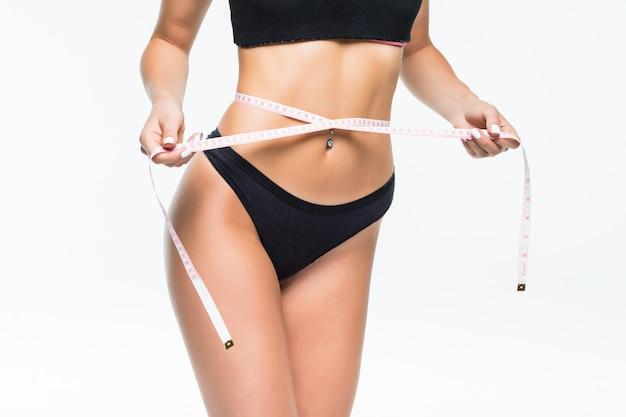 白い壁に分離されたメーターテープで腰を測定黒い下着の女 無料写真
