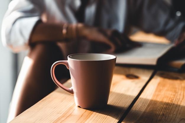 Женщина утром пьет кофе и читает старую книгу в белой рубашке Premium Фотографии