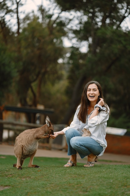 Женщина в заповеднике играет с кенгуру Бесплатные Фотографии
