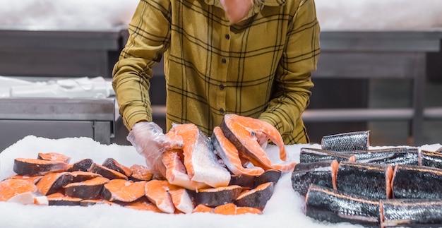 スーパーマーケットの女性。サケの魚を手に持った美しい若い女性。 無料写真